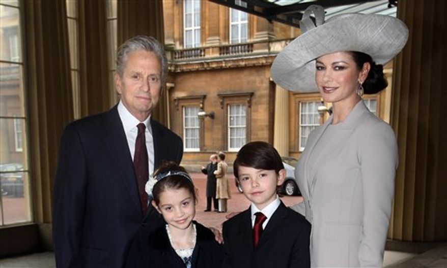 Hollywood actress Catherine Zeta Jones, right, and her husband Michael Douglas, with their children Dylan and Carys, arrive at Buckingham Palace in London where Catherine Zeta Jones will be invested with the royal award as a CBE (Commander of the Order of the British Empire) by the Prince of Wales,  Thursday Feb. 24, 2011.  The Welsh-born actress who became an Oscar-winning star will receive the honour for services to the film industry and to charity. (AP Photo / Lewis Whyld)