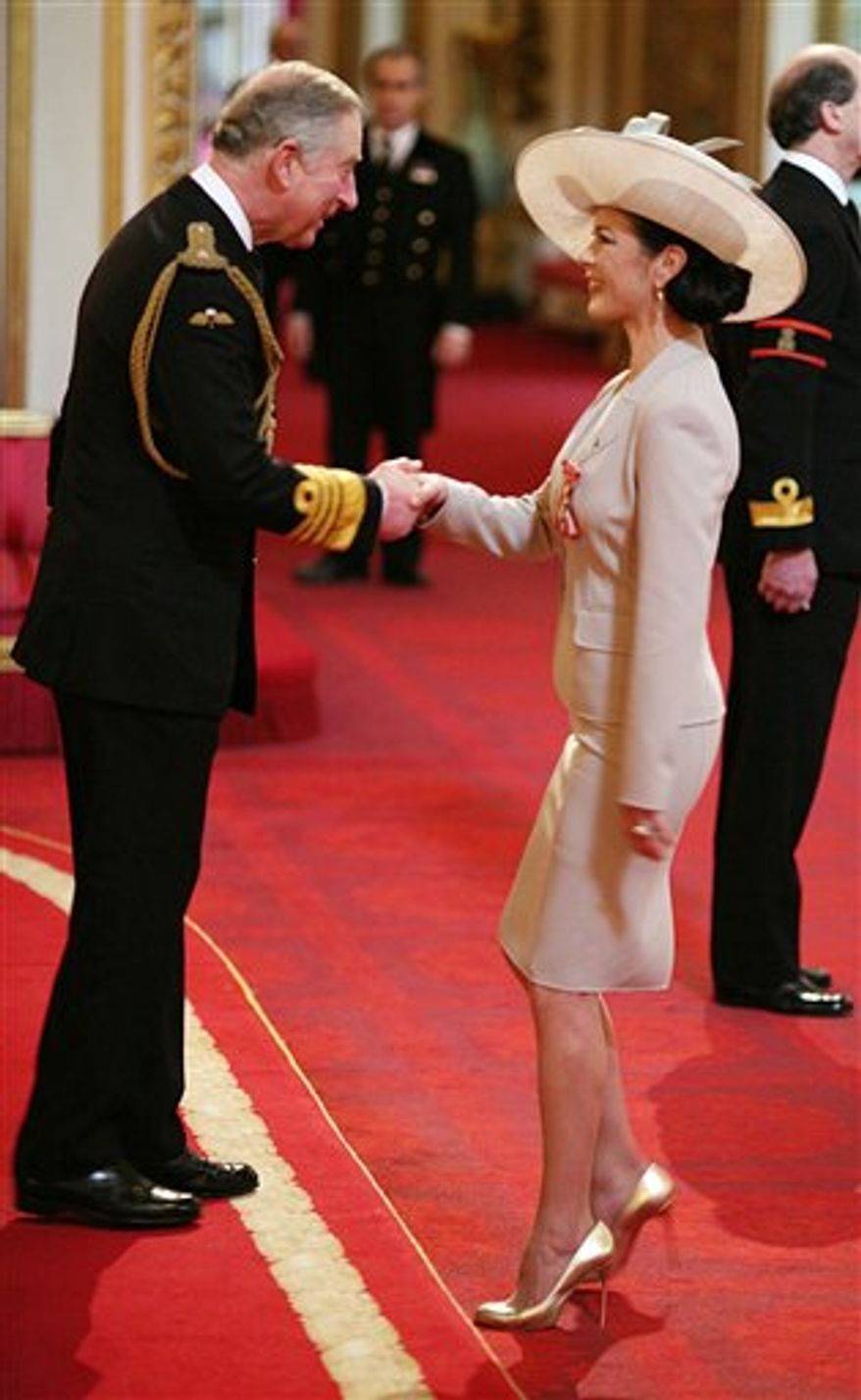 Hollywood actress Catherine Zeta Jones, right,  is invested as a Commander of the British Empire (CBE) by Prince Charles at Buckingham Palace in London, Thursday Feb. 24, 2011.  The Oscar-winning Welsh-born actress receives the royal honour for her services to the film industry and to charity. (AP Photo / Lewis Whyld, PA) UNITED KINGDOM OUT - NO SALES - NO ARCHIVES