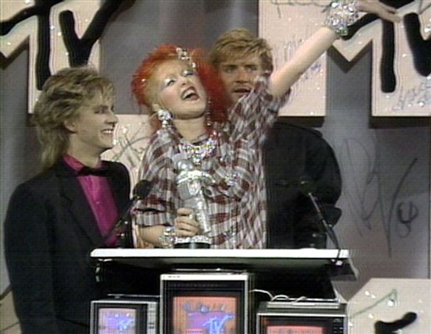 """In this Sept. 14, 1984 image from video released by MTV, singer Cyndi Lauper is flanked by members of Duran Duran, Nick Rhodes, left, and Simon Le Bon as she accepts the award for best female video for """"Girls Just Want to Have Fun""""  during the MTV Video Music Awards at Radio City Music Hall in New York. (AP Photo/MTV) NO SALES"""