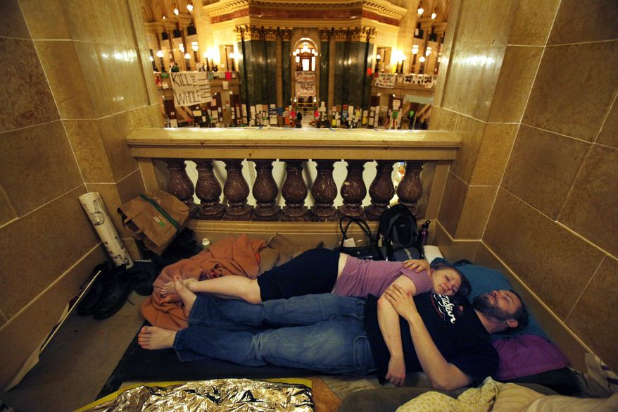 Opponents of Wisconsin Gov. Scott Walker's bill to eliminate collective bargaining rights for many state workers sleep in the Capitol in Madison, Wis., near midnight on Wednesday, Feb. 23, 2011, after a day of protesting. (AP Photo/The Post-Crescent, Sharon Cekada)