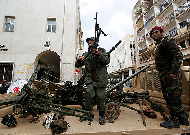 Gunmen prepared to fight against Libyan leader Moammar Gadhafi stand on a small military truck with weapons taken from a Libyan military base, in Benghazi, Libya, on Thursday Feb. 24, 2011. Army units and militiamen loyal to Moammar Gadhafi struck back Thursday against rebellious Libyans who have risen up in cities close to the capital, attacking a mosque where many were holding an anti-government sit-in and battling others who seized control of an airport. Medical officials said 15 people were killed in the clashes. (AP Photo/Hussein Malla)