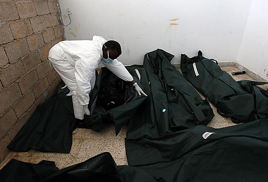 A Libyan mortuary assistant inspects an unidentified calcinated body of a person killed during last week's demonstrations against Libyan leader Moammar Gadhafi, at a morgue, in Benghazi, Libya, Thursday Feb. 24, 2011. (AP Photo/Hussein Malla)