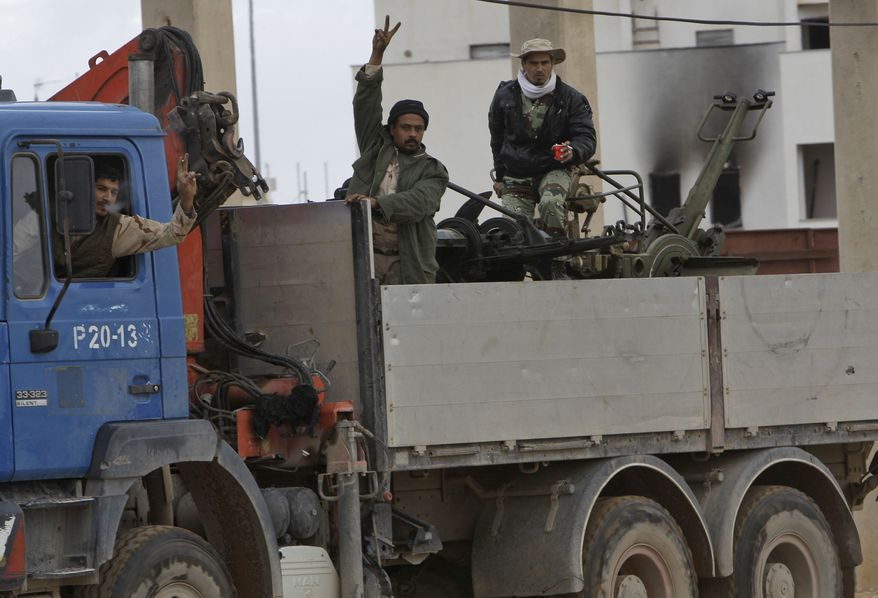 Libyan gunmen flash the V signs as they stand on a military truck with an anti-aircraft machine gun at Al-Katiba military base after it fell to anti-Libyan leader Moammar Gadhafi protesters few days ago, in Benghazi, Libya, on Thursday Feb. 24, 2011. (AP Photo/Hussein Malla)