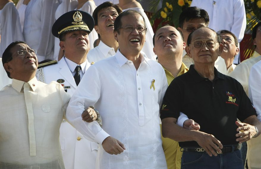 """Philippine President Benigno Aquino III, center, Vice-President Jejomar Binay, left, and former President Fidel Ramos, right, link arms as they sing a patriotic song to celebrate the 25th anniversary of People Power Friday Feb. 25, 2011, at the People Power Monument along EDSA highway at suburban Quezon city, northeast of Manila, Philippines. Mr. Ramos was one of the leaders of the nearly bloodless four-day people power revolution 25 years ago that ousted the late strongman Ferdinand Marcos from 20-year rule and helped install Aquino's mother Corazon """"Cory"""" Aquino to the presidency. (AP Photo/Bullit Marquez)"""