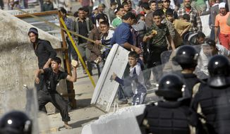 Iraqi anti-government protesters throw stones at riot police during a demonstration in Baghdad Friday, Feb. 25, 2011. Thousands marched on government buildings and clashed with security forces in cities across Iraq on Friday, in the largest and most violent anti-government protests here since political unrest began spreading in the Arab world several weeks ago. (AP Photo/Hadi Mizban)