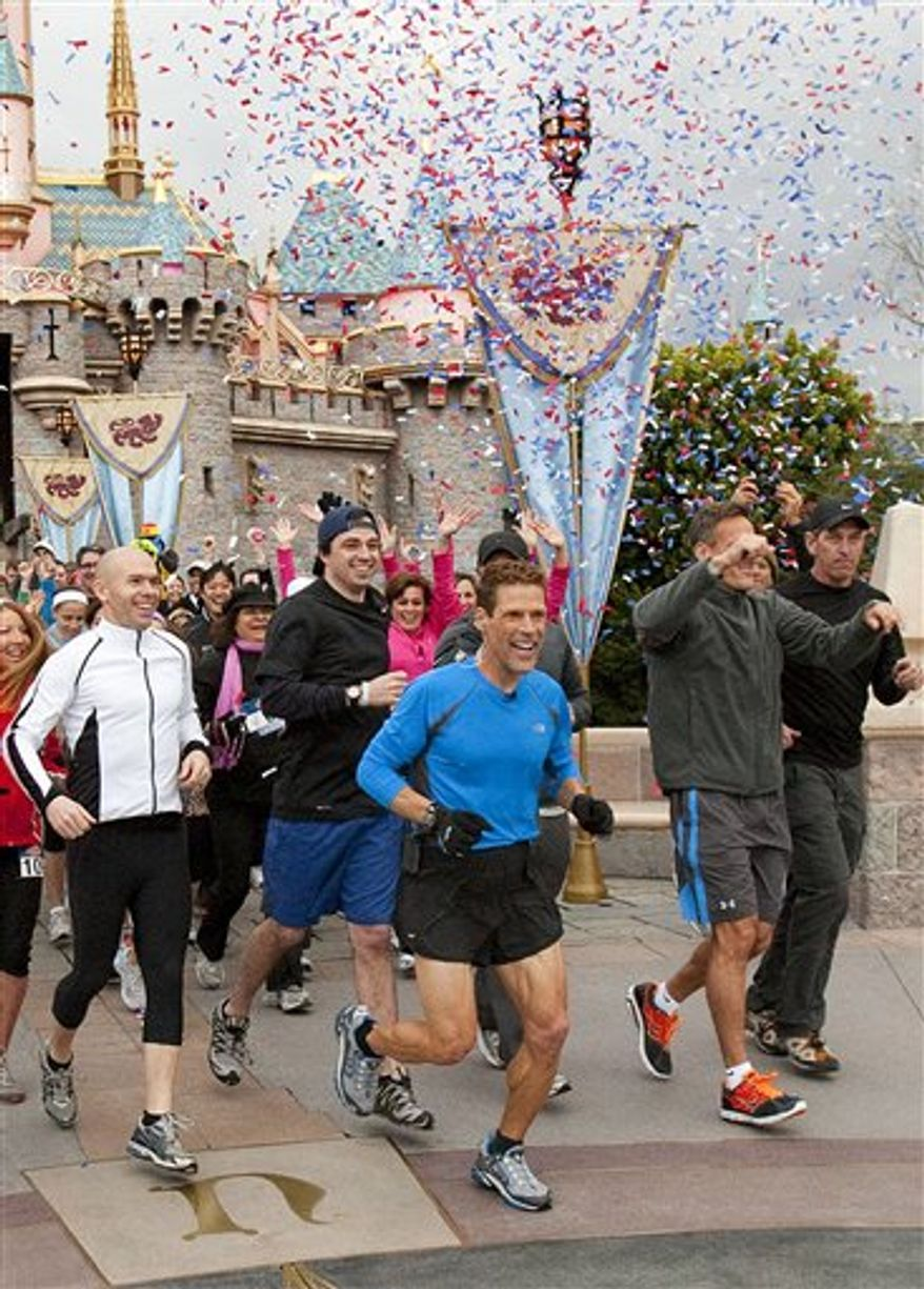 "In this publicity image released by Disneyland, marathoner Dean Karnazes, center, starts out his 3,000-mile run across the country at Disneyland park in Anaheim, Calif., Friday, Feb. 25, 2011.  His departure was aired on the morning talk show ""Live! With Regis and Kelly."" Karnazes is promoting fitness for Americans and young people in particular. The weekday talk show will air updates from his coast-to-coast road trip. It is scheduled to end May 11 when Karnazes is welcomed by co-hosts Kelly Ripa and Regis Philbin to the show's New York studio.  (AP Photo/Disneyland, Paul Hiffmeyer)"