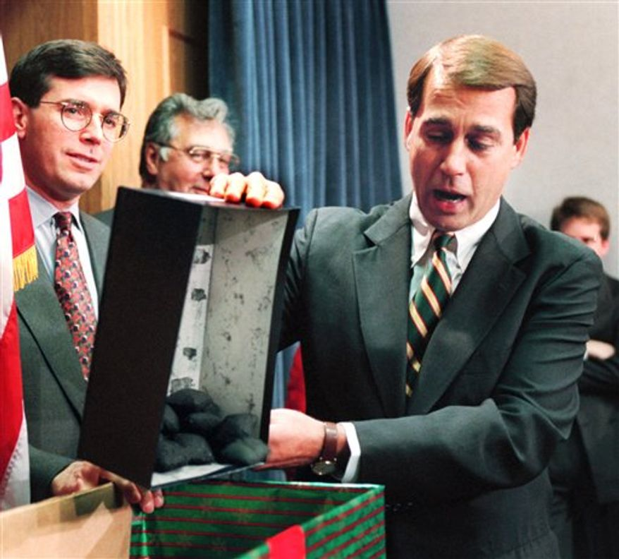 FILE - In this Dec. 21, 1995, file photo Rep. John Boehner, R-Ohio, dumps out coal, his so-called Christmas gift to President Clinton, during a news conference on the federal budget on Capitol Hill. The White House and Congressional Republicans tried to restart balanced budget talks after the sixth day of a partial government shutdown. Then, as now in 2011, a Democratic president clashed over spending priorities with a recently installed Republican House majority. (AP Photo/Denis Paquin, File)