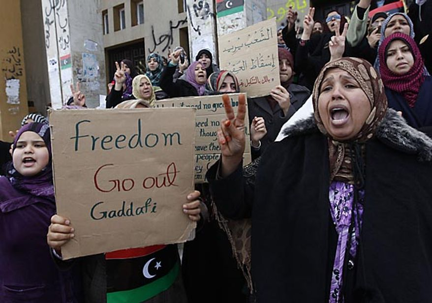 Protesters shout slogans against Libyan leader Moammar Ghadafi during the demonstration before the Friday prayer in Benghazi, Libya, on Friday Feb. 25, 2011. Militias loyal to Col. Gadhafi opened fire on protesters streaming out of mosques in the Libyan capital on Friday, demanding the regime's ouster, witnesses said, reporting at least four killed. Across rebellious cities in the east, tens of thousands held rallies in support of the first Tripoli protests in days. (AP Photo/Hussein Malla)