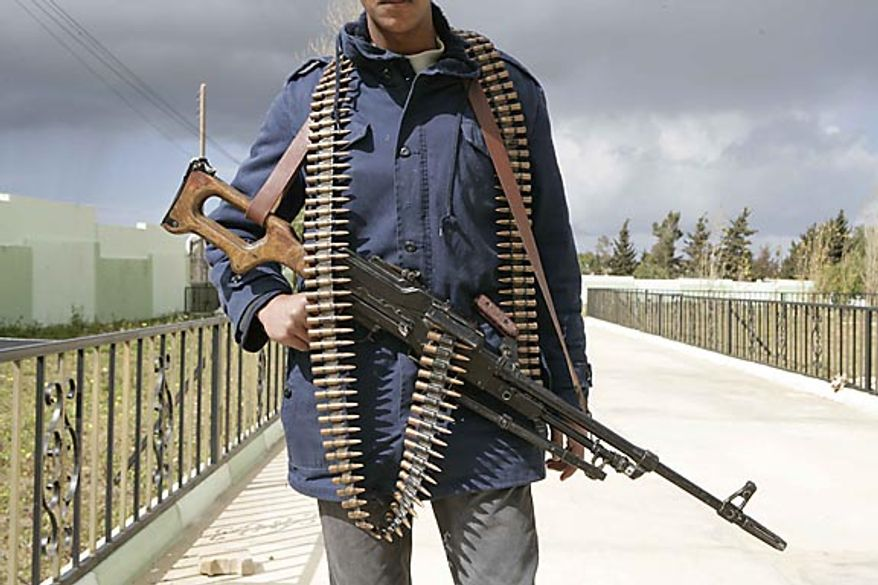 In this photo released by China's Xinhua News Agency, a man holding an automatic machine gun poses in the east Libyan city of Albayda Thursday, Feb. 24, 2011. (AP Photo/Xinhua, Nasser Nouri)