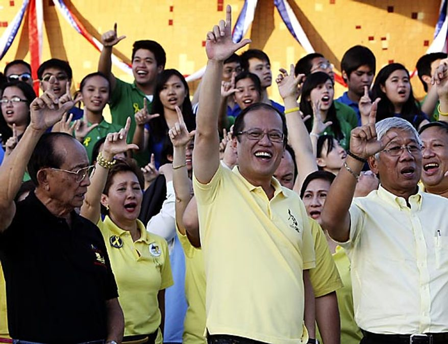 "Philippine President Benigno Aquino III, center, former President Fidel Ramos, left, and Defense Chief Voltaire Gazmin, flash the ""L"" sign (for Laban which means Fight!) during the celebration of the 25th anniversary of the  People Power revolution Friday Feb. 25, 2011 at the People Power Monument along EDSA highway at suburban Quezon city northeast of Manila, Philippines. The nearly bloodless four-day people power revolution 25 years ago saw the ouster of the late strongman Ferdinand Marcos from 20-year rule and helped install current President Benigno Aquino III's mother Corazon ""Cory"" Aquino to the presidency. (AP Photo/Bullit Marquez)"