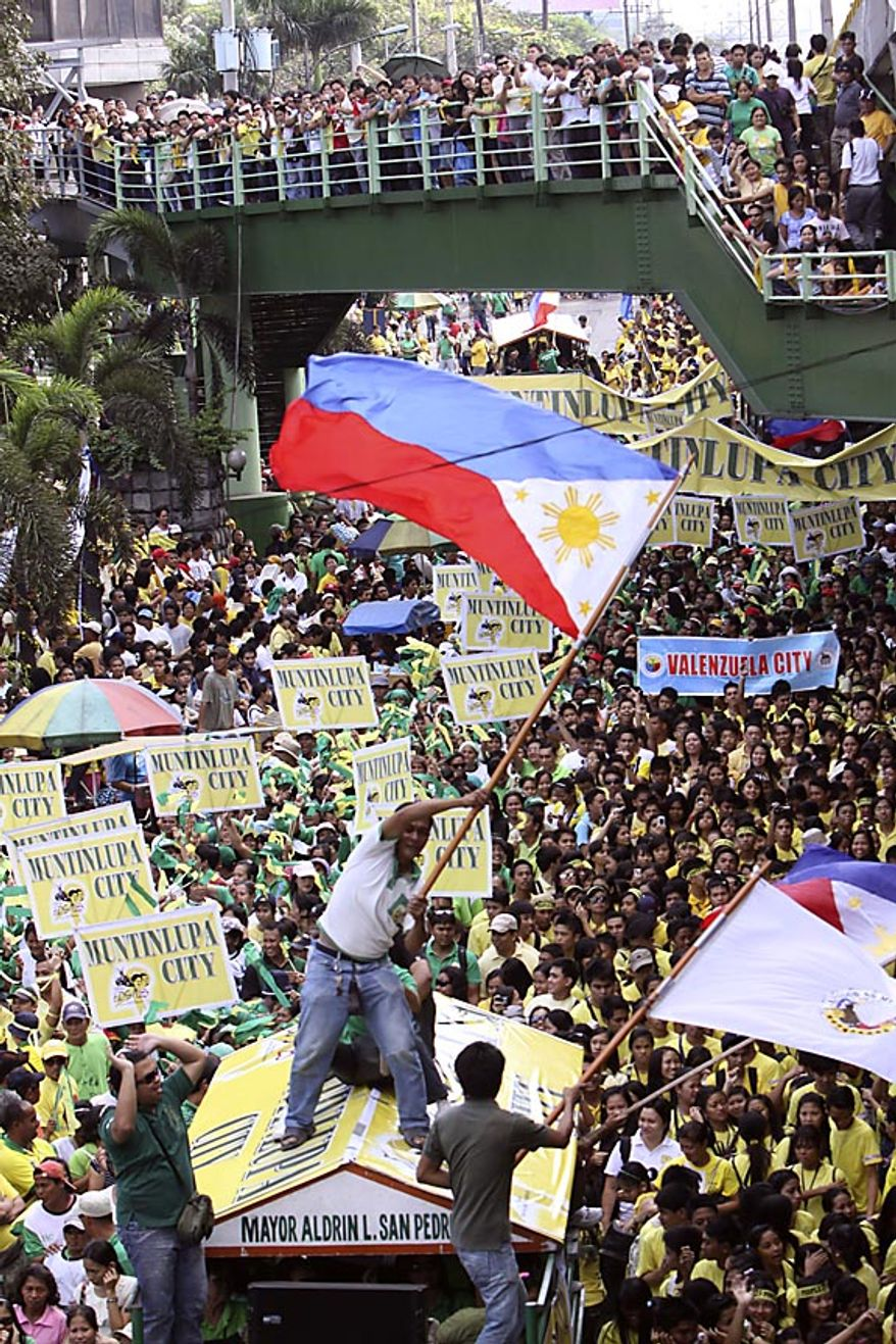 "A man on top of a truck waves the Philippine flag, re-enacting ""People Power"" revolution during the celebration of its 25th anniversary Friday, Feb. 25, 2011, in suburban Pasig City east of Manila, Philippines. The nearly bloodless four-day people power revolution 25 years ago saw the ouster of the late strongman Ferdinand Marcos from 20-year rule and helped install now President Benigno Aquino III's mother Corazon ""Cory"" Aquino to the presidency. (AP Photo/Pat Roque)"