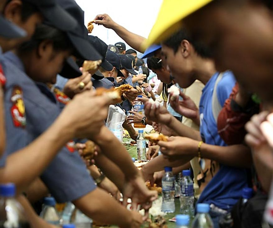 "Philippine National Police are joined by civilians as they take their lunch known as ""boodle fight"" in the continuing celebration of the 25th anniversary of People Power Friday Feb. 25, 2011, along EDSA highway at suburban Quezon city northeast of Manila, Philippines. The nearly bloodless four-day people power revolution 25 years ago saw the ouster of the late strongman Ferdinand Marcos from 20-year rule and helped install now President Benigno Aquino III's mother Corazon ""Cory"" Aquino to the presidency. (AP Photo/Bullit Marquez)"