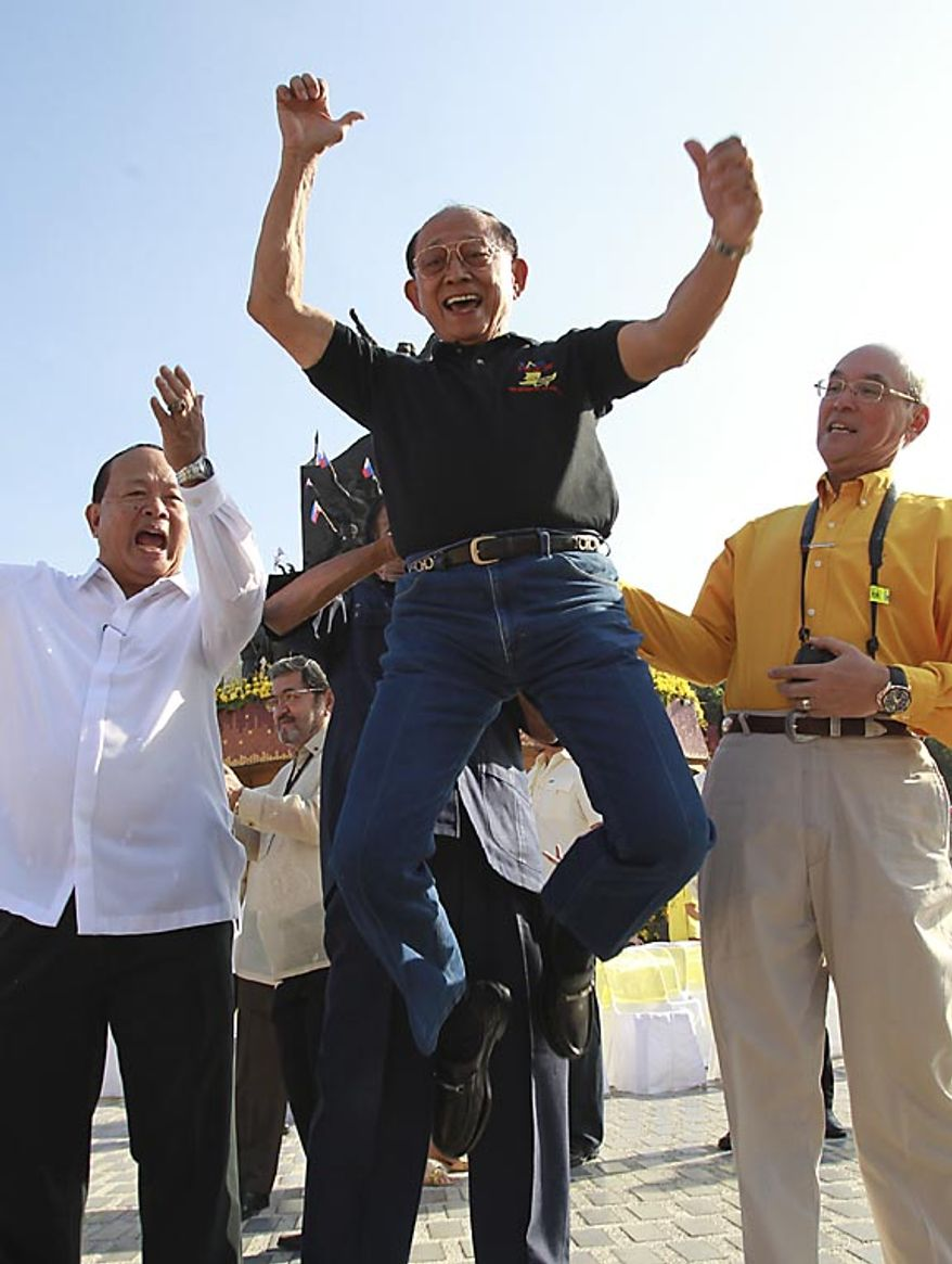 Former Philippine President Fidel Ramos, center, re-enacts the famous jump he made 25 years ago during the 25th anniversary celebrations of People Power on Friday, Feb. 25, 2011, at the People Power Monument along EDSA highway at suburban Quezon city, northeast of Manila. Mr. Ramos, one of the leaders of the nearly bloodless four-day people power revolution, made the jump following a premature announcement that the late strongman Ferdinand Marcos had fled the country.  (AP Photo/Bullit Marquez)