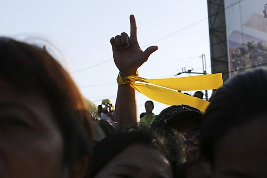"Civilians flash the ""L"" sign (for Laban which means Fight!) as they sing patriotic song during the celebration of the 25th anniversary of the People Power revolution Friday Feb. 25, 2011, at the People Power Monument along EDSA highway at suburban Quezon city northeast of Manila, Philippines. The nearly bloodless four-day people power revolution 25 years ago saw the ouster of the late strongman Ferdinand Marcos from 20-year rule and helped install current President Benigno Aquino III's mother Corazon ""Cory"" Aquino to the presidency. (AP Photo/Bullit Marquez)"