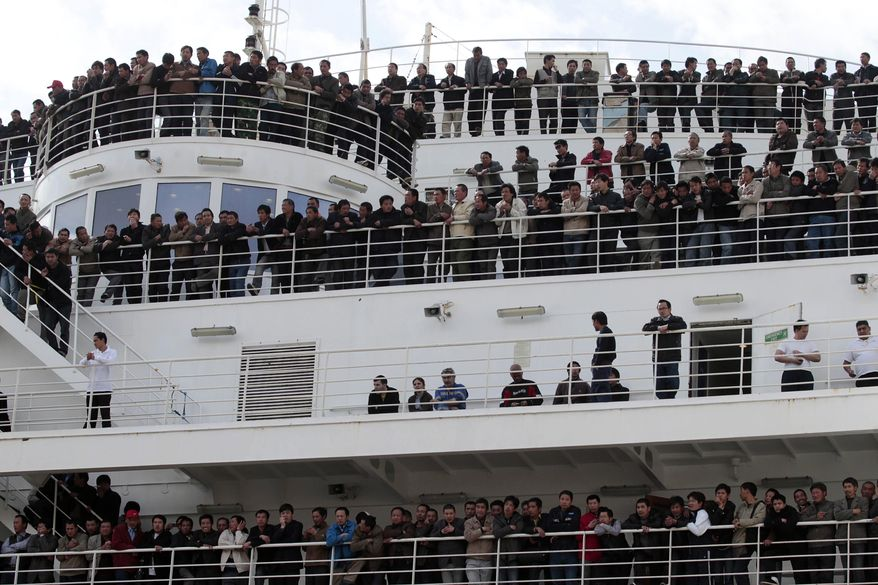 """Chinese citizens wait aboard the """"Palermo Grimaldi"""" ferry at the harbor in Valletta, Malta, Saturday, Feb. 26, 2011, after being evacuated from Benghazi, Libya. (AP Photo/Gregorio Borgia)"""