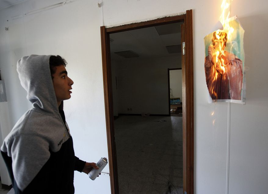 A Libyan youths looks at a portrait of Libyan leader Moammar Ghadafi which he set alight in a destroyed conference room inside the Brega oil complex, in Brega, eastern of Libya, Saturday, Feb. 26, 2011. The embattled regime of Moammar Gadhafi is arming civilian supporters to set up checkpoints and roving patrols around the Libyan capital to control movement and quash dissent, residents said Saturday. (AP Photo/Hussein Malla)