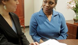 Kelley Williams-Bolar (right) works with lawyer Angelina Jackson earlier this month in Cincinnati. Williams-Bolar was accused of records tampering after prosecutors said she used her father's address to enroll her daughters in the Copley-Fairlawn district in Akron, Ohio. (Associated Press)