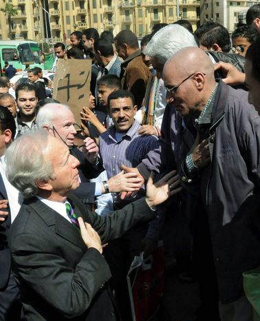 REACHING OUT: Sens. John McCain and Joseph I. Lieberman discuss plans for Libya at Tahrir Square in Cairo on Sunday. (Associated Press)
