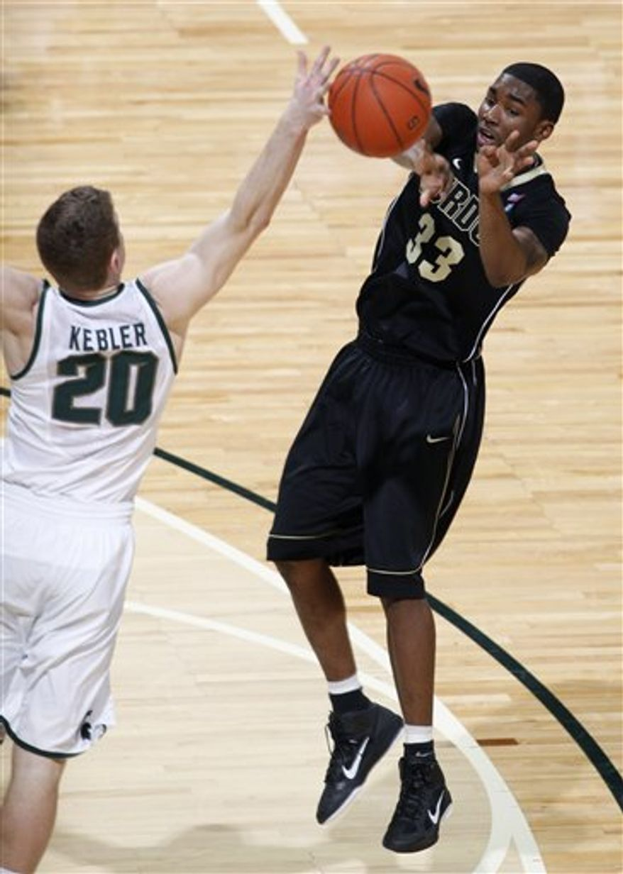 Purdue's E'Twaun Moore (33) passes against Michigan State's Mike Kebler (20) during the first half of an NCAA college basketball game, Sunday, Feb. 27, 2011, in East Lansing, Mich. (AP Photo/Al Goldis)
