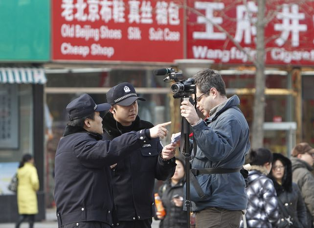 Chinese police ask an Associated Press cameraman to leave the area near the shopping street of Wangfujing in Beijing on Sunday, Feb. 27, 2011. Large numbers of police and the use of new tactics such as shrill whistles and street cleaners squelched any overt protests in China after calls for more peaceful gatherings modeled on recent democratic movements in the Middle East. (AP Photo/Andy Wong)