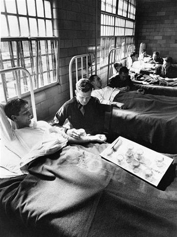 """FILE - In this Oct. 9, 2007 file picture, Edward Anthony, left, describes medical experiments that were performed on him while he was an inmate at Philadelphia's Holmesburg Prison, as author Allen Hornblum listens in Philadelphia. Anthony's recollections as a test subject during the mid-1960s, and of struggling with the physical and psychological troubles that followed, are the subjects of """"Sentenced to Science,"""" a book by Hornblum. (AP Photo/Rusty Kennedy, File)"""