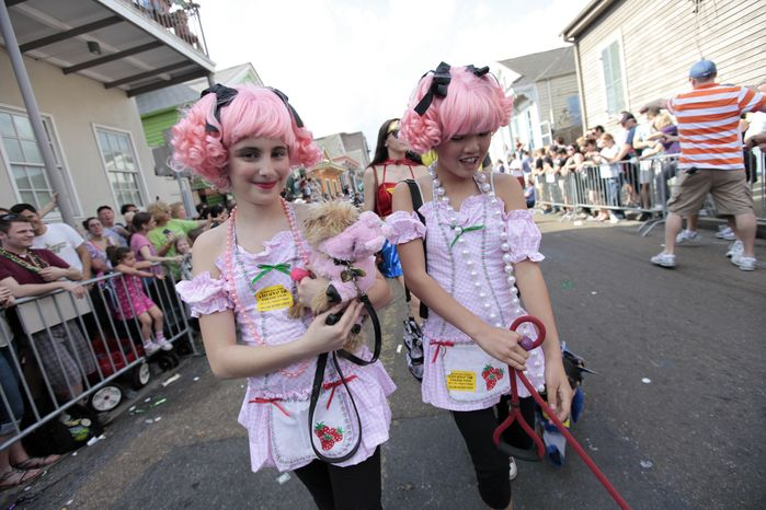 Young girls and their dogs parade through the French Quarter during the Krewe of Barkus Mardi Gras parade in New Orleans on Sunday. The parade of dogs and their owners, a twist on the Krewe of Bacchus, benefits animal welfare organizations. (Associated Press)