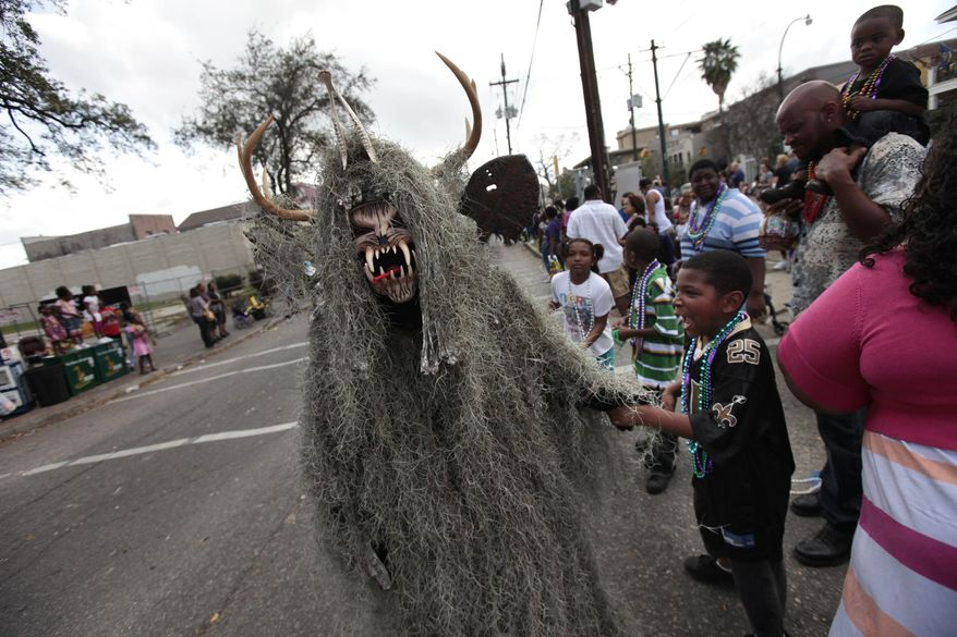 A man dressed up as a moss monster greets children during the Krewe of Carrollton Mardi Gras parade in New Orleans on Sunday. (Associated Press)