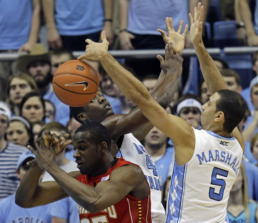North Carolina's Harrison Barnes, rear, and Kendall Marshall (5) struggle for a rebound with Maryland's James Padgett during the first half of an NCAA college basketball game in Chapel Hill, N.C., Sunday, Feb. 27, 2011. (AP Photo/Gerry Broome)