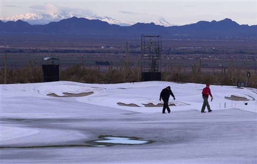 Superintendents at the Ritz Carlton Golf Club check the playing surface on the second fairway for saturation levels after snow fell early in the morning before the finals of the Match Play Championship golf tournament Sunday, Feb. 27, 2011, in Marana, Ariz. The snow was not expected to stop the golf, however. The sun began to break through an hour later, and tournament director Mark Russell did not anticipate any delays.  (AP Photo/Julie Jacobson)