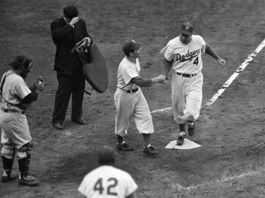 """FILE - In this Oct. 2, 1955, file photo, fans and teammates applaud Brooklyn Dodgers' Duke Snider (4) after his fifth-inning home run against the New York Yankees in a World Series baseball game in the Brooklyn borough of New York. It was Snider's second homer of the game. Snider, 84, died early Sunday, Feb. 27, 2011, of what the family called natural causes at the Valle Vista Convalescent Hospital in Escondido, Calif. Snider was part of the charmed """"Boys of Summer"""" with the Dodgers in the late 1940s and 1950s. He helped lead Brooklyn to its only World Series championship in 1955. (AP Photo/File)"""