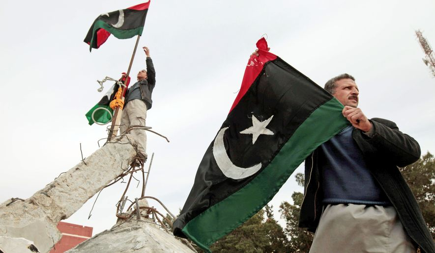 Libyans wave the country's monarchist-era flag Monday on a monument in the southwestern town of Nalut. The town is now under the control of Libyan anti-government forces. The protesters hope to take control of the entire country without outside intervention. (Associated Press)