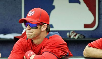 Washington Nationals' Bryce Harper watches from the dugout Monday at the start of a spring-training baseball game against the New York Mets in Port St. Lucie, Fla. The 18-year-old outfielder got into the game but struck out twice in two at-bats against major league pitching. (Associated Press)