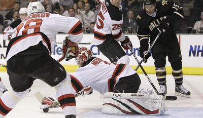 New Jersey Devils goalie Johan Hedberg, of Sweden, traps a loose puck as Anton Volchenkov, front, of Russia and Jason Arnott (25) help against pressure from Dallas Stars right wing Jamie Langenbrunner (15) in the first period of an NHL hockey game Tuesday, Feb. 22, 2011, in Dallas. (AP Photo/Tony Gutierrez)