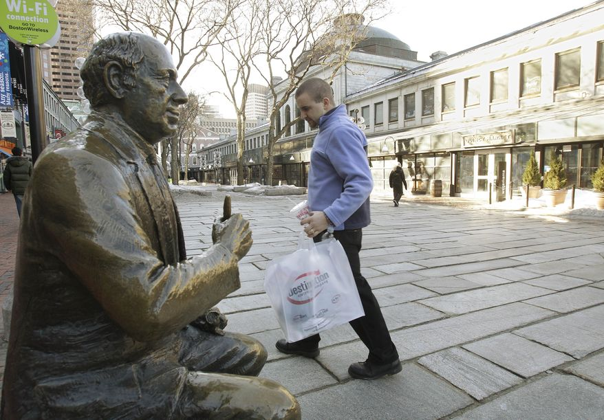 A shopper walks past a bronze sculpture of famed Boston Celtics coach Red Auerbach at Qunicy Market in downtown Boston on Monday, Feb. 14, 2011. (AP Photo/Stephan Savoia)
