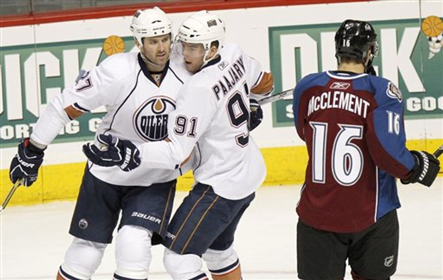 Edmonton Oilers left wing Dustin Penner (27) is congratulated by teammate Magnus Paajarvi (91), of Sweden, for scoring a goal while Colorado Avalanche center Jay McClement (16) skates by during the first period of an NHL hockey game in Denver, Wednesday, Feb. 23, 2011. (AP Photo/Barry Gutierrez)