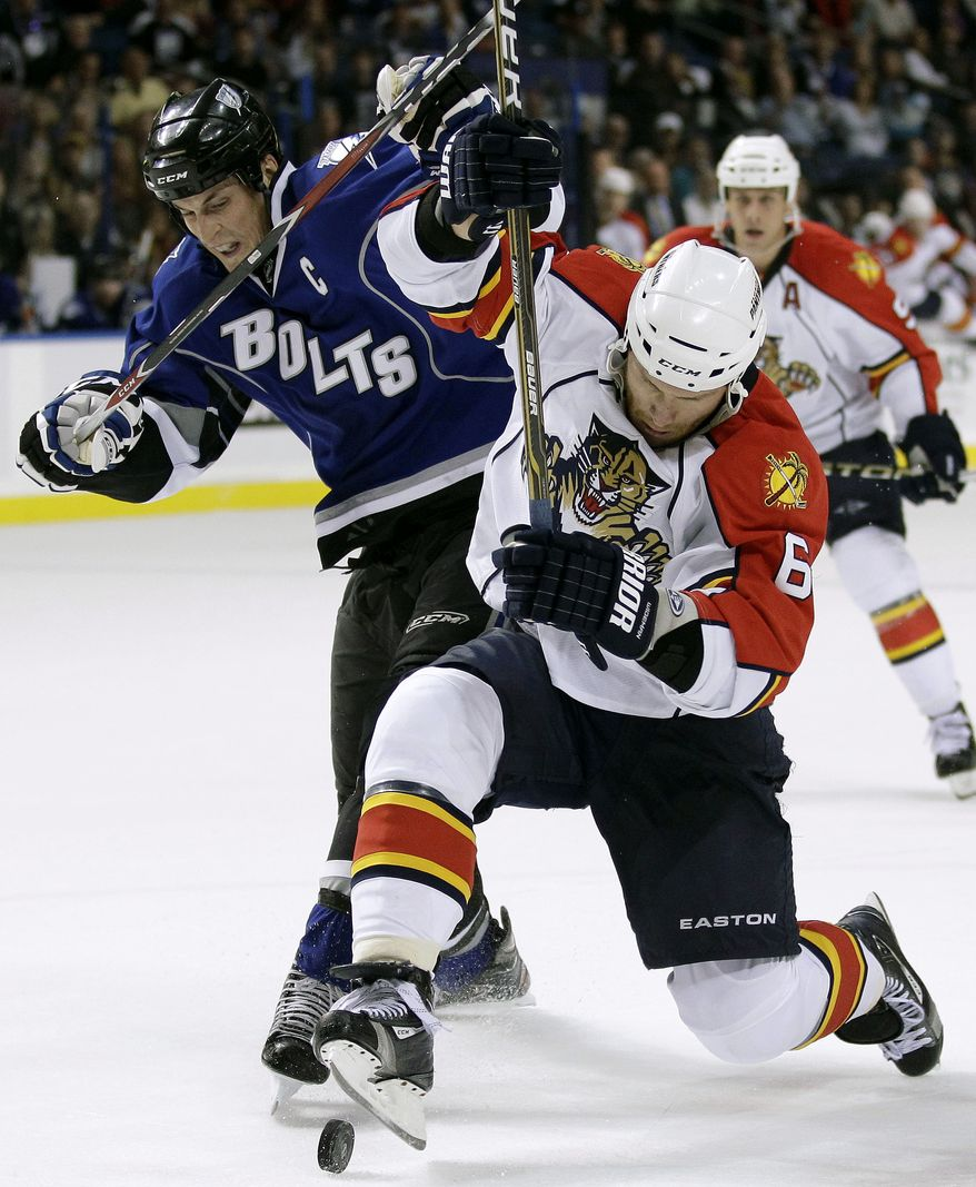 Florida Panthers defenseman Dennis Wideman (6) and Tampa Bay Lightning center Vincent Lecavalier (4) battle for a loose puck during the second period of an NHL hockey game in Tampa, Fla., Saturday, Feb. 19, 2011. (AP Photo/Chris O'Meara)