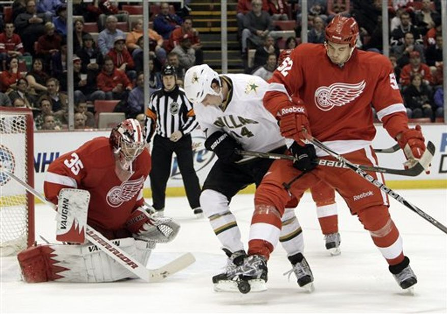 Dallas Stars left wing Jamie Benn (14), and Detroit Red Wings defenseman Jonathan Ericsson (52), of Sweden, battle for the puck in front of Detroit Red Wings goalie Jimmy Howard (35) in the second period of an NHL hockey game in Detroit, Thursday, Feb. 24, 2011. (AP Photo/Paul Sancya)