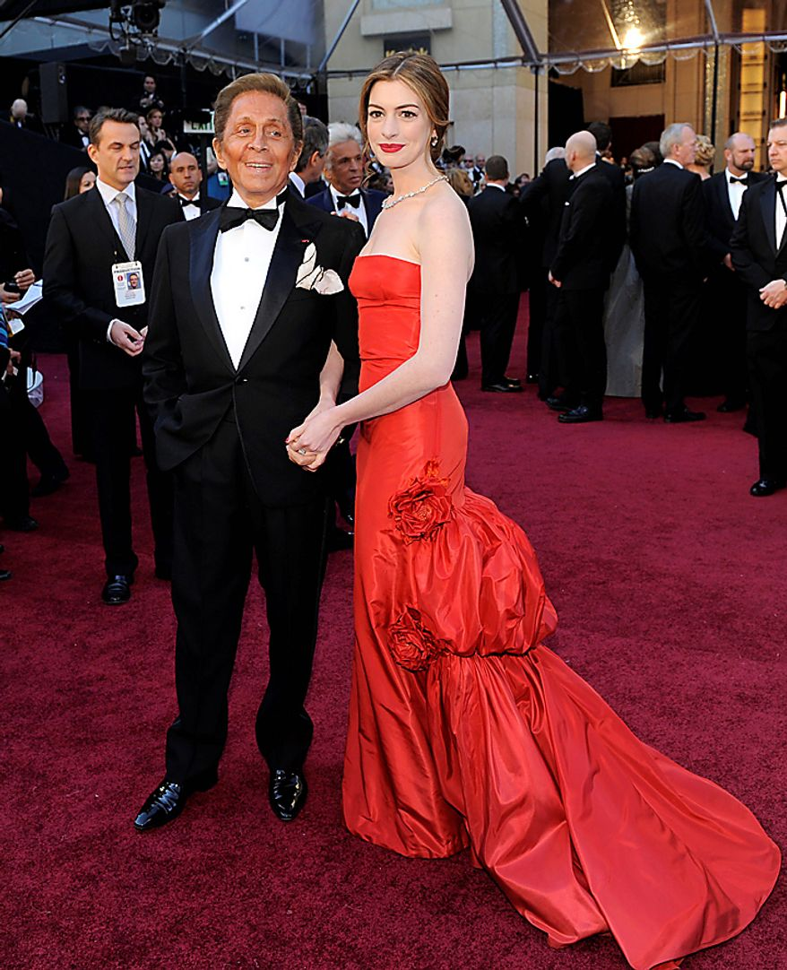Designer Valentino poses with Oscar co-host Ann Hathaway  on the red carpet before the 83rd Academy Awards on Sunday, Feb. 27, 2011, in the Hollywood section of Los Angeles. (AP Photo/Chris Pizzello)