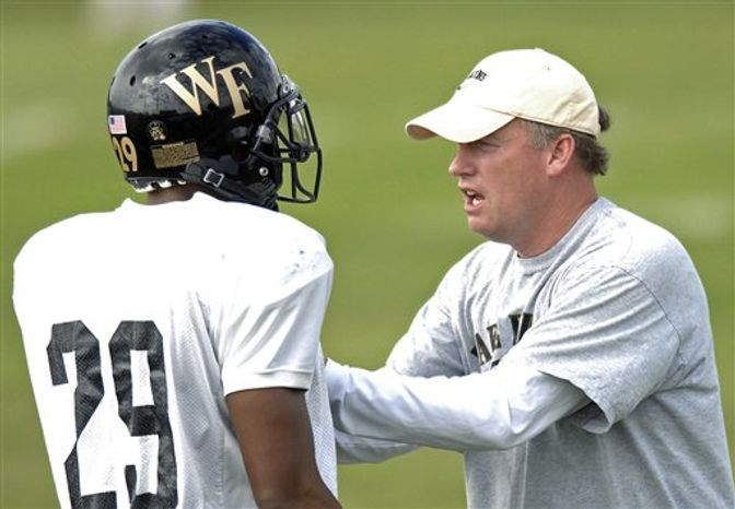 FILE - In this Dec. 29, 2006 file photo, Wake Forest linebacker coach Brad Lambert, right, speaks with cornerback Kerry Major during NCAA college football practice in Davie Fla. UNC-Charlotte hired Lambert on Tuesday, March 1, 2011, as head coach for their fledgling football program. (AP Photo/Steve Mitchell, File)