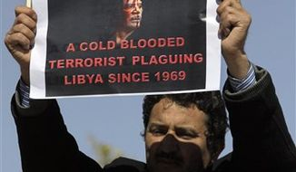 A Libyan anti-government protester, holds a monarchist-era flag, and a poster expressing his accusations, during a demonstration against Libyan leader Moamar Gadhafi, in the southwestern town of Nalut, Libya, Tuesday, March 1, 2011.  The town is currently in control of the Libyan anti-government forces. (AP Photo/Lefteris Pitarakis)