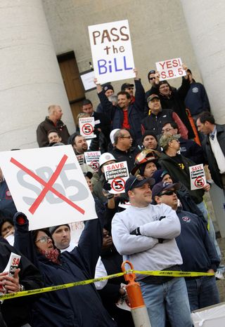 Both supporters and opponents of Senate Bill 5 wait in line to enter the general Senate session Wednesday in Columbus, Ohio. The Senate passed the bill that would strip public employees of collective bargaining rights. (Associated Press)