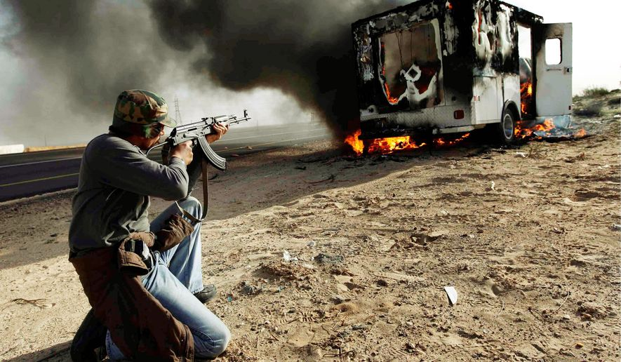 A Libyan rebel shoots toward a burning vehicle that once contained troops loyal to Col. Moammar Gadhafi. The gunfire was in celebration of regime opponents' control of the town of Brega, which has a key oil installation. (Associated Press)
