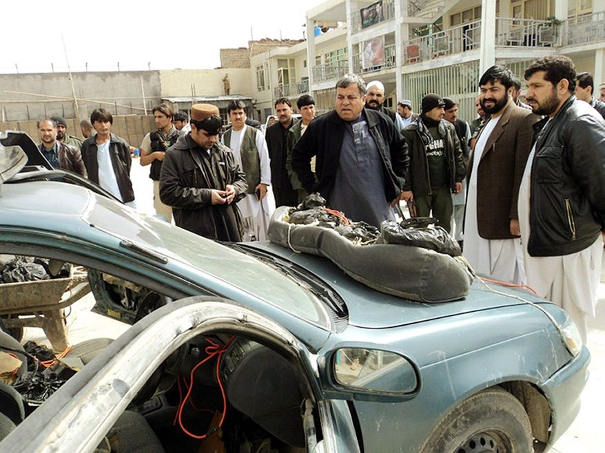 Kandahar, Afghanistan, Gov. Tooryalai Wesa (center) looks over weapons discovered by Afghan security forces, who seized a car in the city loaded with explosives and weapons. (Kandahar Media Information Center via Associated Press)