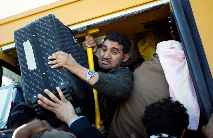 FLEEING FIGHTING: Egyptians who worked in Libya and are trying to get away from the emerging civil war there jam their belongings into a bus Thursday as they leave the country at the border near Ras Ajdir, Tunisia. (Associated Press)