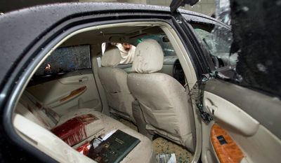 A Pakistani man examines the blood-stained car of Shahbaz Bhatti, minister for minorities affairs and the only Christian in the Cabinet, on Wednesday in Islamabad. Mr. Bhatti was fatally shot in the car near his mother's house. (Associated Press)