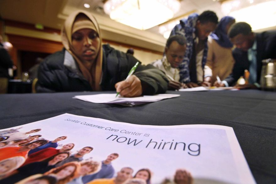 In this March 1, 2011, photo, Mariam Bario, recently relocated to Seattle from Kenya, fills out an application with others at a job fair, in SeaTac, Wash. Employers in February hired at the fastest pace in almost a year and the unemployment rate fell to 8.9 percent -- a nearly two-year low. (AP Photo/Elaine Thompson)