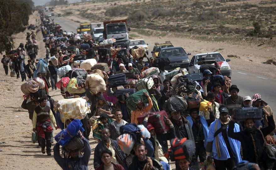 Men from Bangladesh, who used to work in Libya but recently fled the unrest, walk with their belongings alongside a road, as they head to a refugee camp after crossing the Tunisia-Libyan border, in Ras Ajdir, Tunisia, Friday, March 4, 2011. (AP Photo/Emilio Morenatti)