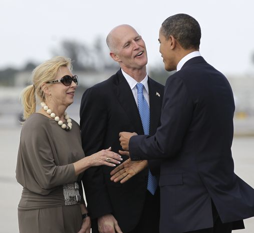 President Obama is greeted by Florida Gov. Rick Scott and his wife Ann upon his arrival to Miami International Airport on Friday, March, 4, 2011. (AP Photo/Pablo Martinez Monsivais)