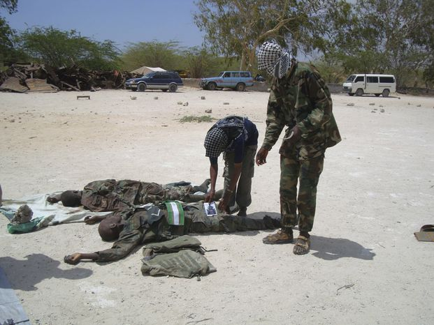 Members of Al Shabaab look at bodies of a Ugandan soldier from the African Union peacekeeping troops based in Mogadishu and of Somali government soldier, Sunday, Feb. 20, 2011 in Mogadishu, Somalia. The two soldiers were killed in fighting that took place in past two days in the Somali capital Mogadishu, between Al Shabaab and Government forces. (AP Photo/Farah Abdi Warsameh)