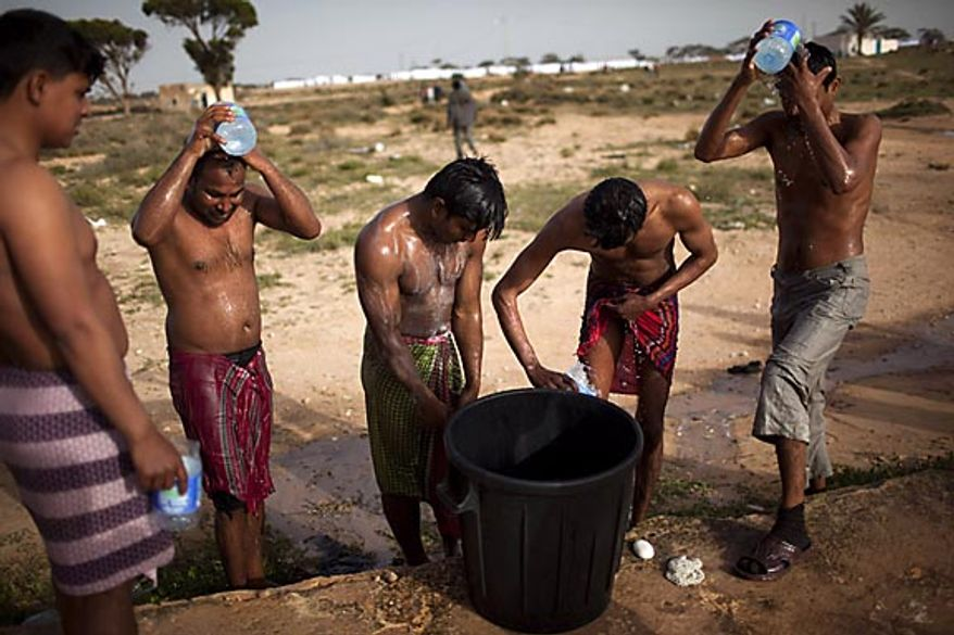 Men from Bangladesh, who used to work in Libya but recently fled the unrest, wash themselves in a refugee camp after crossing the Tunisia-Libyan border, in Ras Ajdir, Tunisia, Friday, March 4, 2011. Many of the men were angry at their government's inaction in aiding their return to Bangladesh. Further adding to their difficulties, many appear to have arrived in Tunisia penniless because their Libyan employers did not pay them or because they were robbed on the way to the border. (AP Photo/Emilio Morenatti)